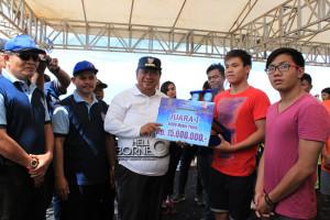 Bupati Penajam Paser Utara, Yusran Aspar saat memberikan hadiah kepada juara pertama putra kelas nasional 6.000 meter OWS 2015, Edward Farid Wijaya (Suherman - Hello Borneo)
