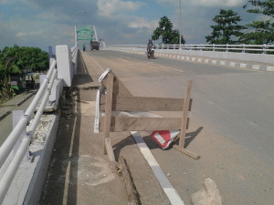 WASPADA. Retakan yang terjadi di Jembatan Kandilo Bahari, kian parah. Apalagi plang peringatan yang dipasangpun sudah ikut rusak (Ajang Araya - Hello Borneo)