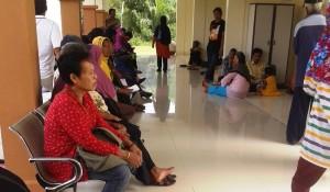 ANTRI. Warga PPU terpaksa duduk di lantai sambil menunggu antrian pelayanan RSUD PPU (Subur - Setkab PPU)