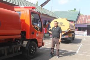 BERSIAP. Kepala BPBD Kabupaten Paser Irwan saat menunjukan mobil tangki yang siap mengangkut persedian air bersih. (Ajang Araya - Hello Borneo)