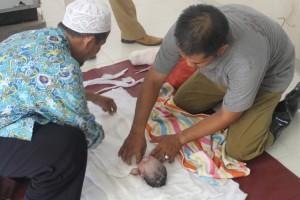 IRONIS. Saat dibersihkan sebelum dikuburkan, jasad bayi perempuan yang ditemukan dalam tong sampah sebelah Masjid Agung Tana Paser. (Ajang Araya - Hello Borneo)