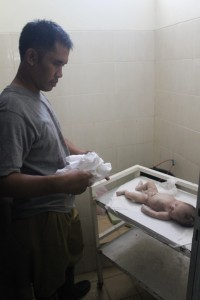 PENYELIDIKAN. Jasad bayi perempuan yang ditemukan dalam TPS, saat dimandikan di RSUD Panglima Sebaya, sebelum dimakamkan di TPU Semumun kilometr 1 lalu.(Ajang Araya - Hello Borneo)