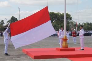 KHIDMAT. Suasana upacara pengibaran bendera merah putih di Kabupaten Paser, dan saat Wakil Bupati Paser Mardikansyah memberikan bendera kepada Sodari Diana Fatihah K yang dipercaya membawa Sang Merah Putih. (MR Saputra - Hello Borneo)