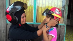DEMI ANAK. Pentingnya menggunakan helm, untuk anak kecil. Agar dapat meminimalisir dari kecelakaan, bukan menghindari surat tilang polisi. Seperti gambar yang di ambil Selasa (1/9) saat seorang ibu memasangkan helm untuk anaknya. (Rapal JKN - Hello Borneo)