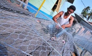 Mengisi kekosongan karena angin kencang, nelayan Kabupaten Paser membuat jala. (Rapal JKN - Hello Borneo)