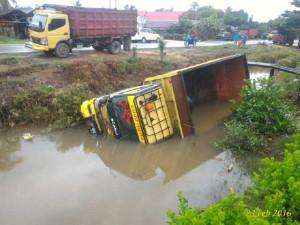 Sebuah truk terguling dan tercebur ke dalam parit besar di sebelah jalan raya Kelurahan Petung, Kecamatan Penajam, Kabupaten Penajam Paser Utara (AH Ari B - Hello Borneo)