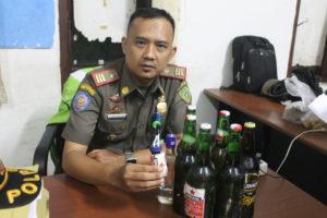 Kasi Operasional Satpol PP Kabupaten Penajam Paser Utara, Denny Hamdansyah bersama barang bukti. (MR Saputra - Hello Borneo)