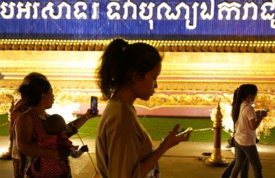 Sejumlah orang berjalan sambil menggunakan ponsel mereka di Phnom Penh, Kamboja, 18 Februari 2021. (Foto: Reuters)