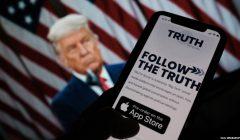 """Seseorang sedang melihat aplikasi """"Truth Social"""" di ponsel, dengan foto mantan presiden AS Donald Trump sebagai latar belakang, di Los Angeles, 20 Oktober 2021. (Foto: AFP/ Chris Delmas)"""