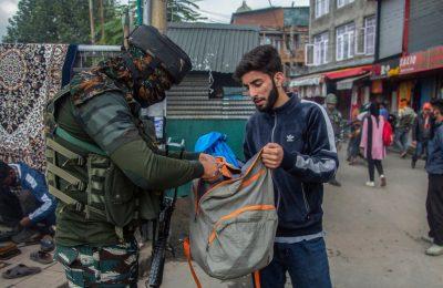 Tentara India tampak mengecek isi tas dari seorang pemuda Kashmir yang berjalan melewati area sibuk di pasar di Srinagar, wilayah Kashmir yang dikontrol oleh India, pada 11 Oktober 2021. (Foto: AP/Mukhtar Khan)