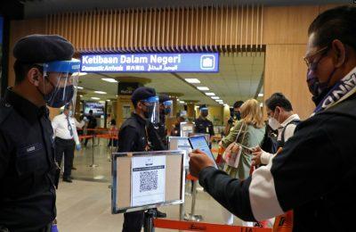 Seorang wisatawan memindai kode QR saat tiba di bandara menyusul pembukaan Langkawi untuk wisatawan domestik di tengah pandemi virus corona COVID-19) di Malaysia, 16 September 2021. (Foto: Lim Huey Teng/Reuters)